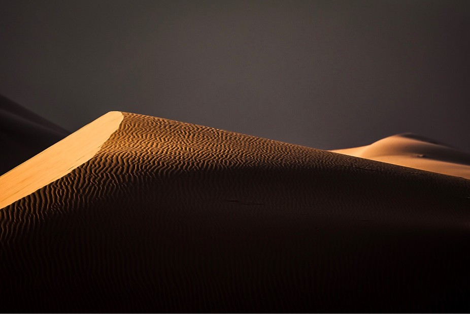 Sunrise in the Desert. The first morning light touches the top of a dune.