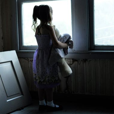 Abandoned Girl Looks out the window