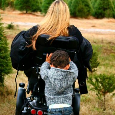 A shot that has an impact.  This little man is helping his Aunt by pushing her chair so that she doesn't get stuck while searching for that perfect Christmas tree.  He only knows that his Aunt. can't always go everywhere he can, so he is always there with a small push.