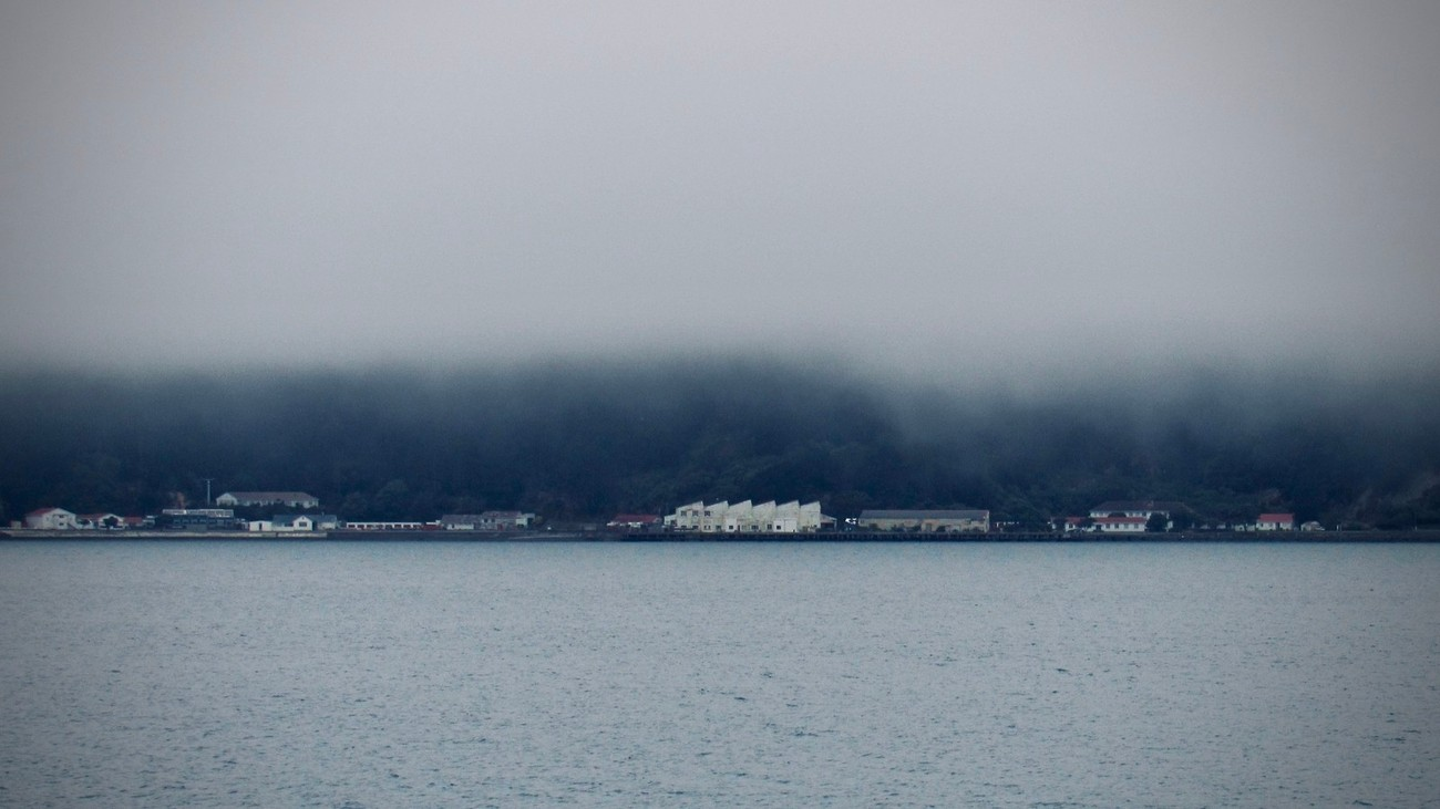 The Shelly Bay Airforce base buildings show through the sea mist shrouding the hills behind, a few light gleam in the dimness of dusk