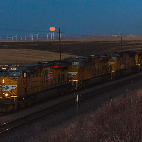 A California-bound Union Pacific intermodal train climbs the steep grade of Sherman Hill in Granite, WY as the moon begins the rise over the horizon.