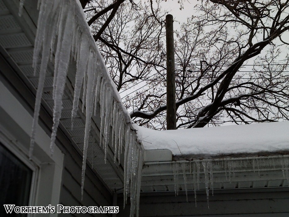 A row of ice sickles forming around the curves of a house just waiting to be broken off.