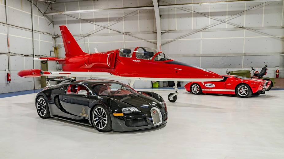 A Bugatti Veyron parked next to an Albatross jet in a hangar.