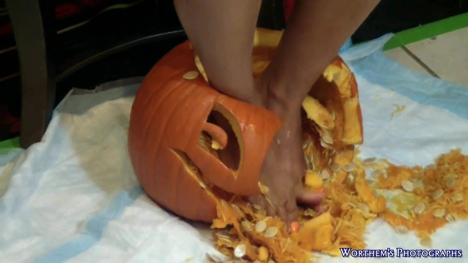 My beautiful model with orange colored toenails is smashing an innocent looking jack-o-lantern with her feet.