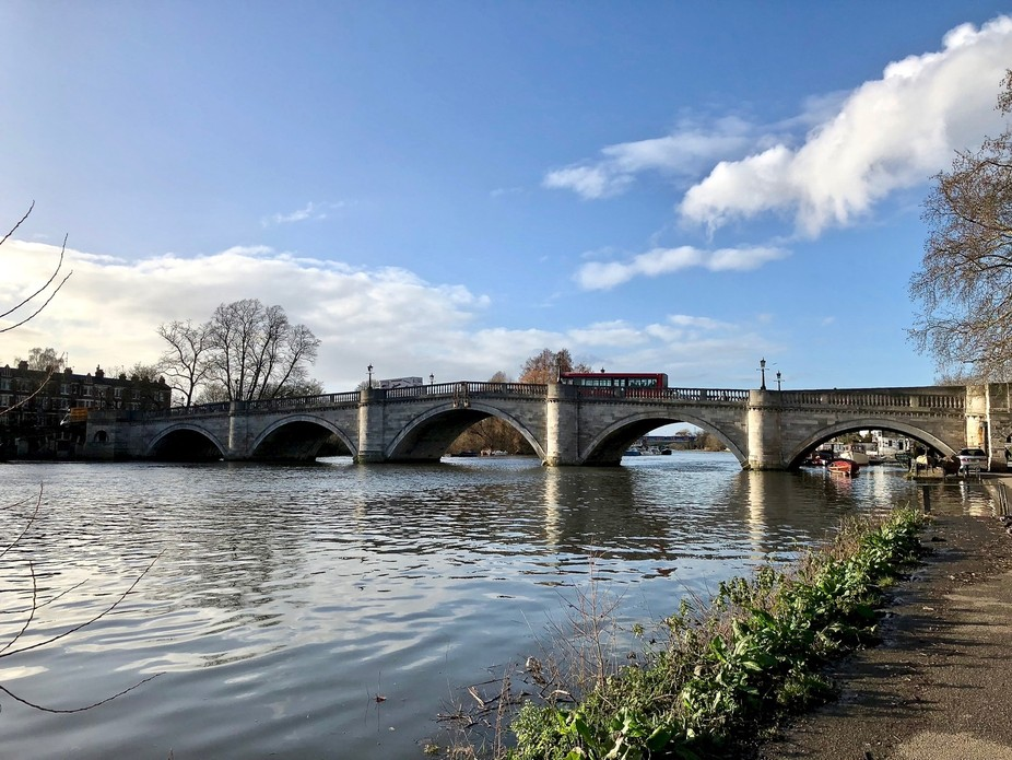 A London red bus crossing Richmond bridge the oldest surviving Thames bridge in London.