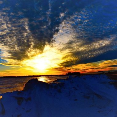 Sunset on the ice glazed snow along the drifted roadway. Nikon D3400 supervivid