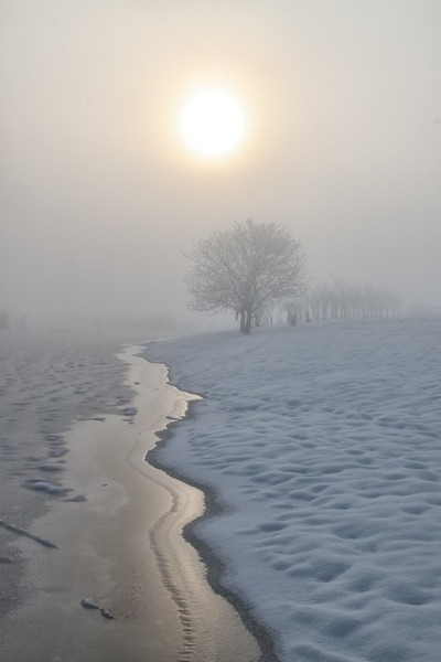 Sun, ice and snow in the fog