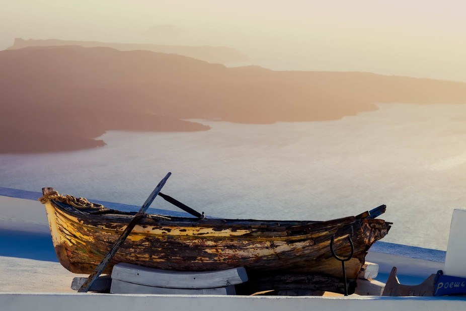 A boat on top of  a rooftop over looking the Ageian sea. Santorini is full of beauty and surpise.