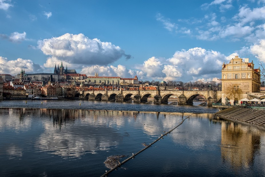 Charles Bridge  in Prague crosses the Vltava river, the present  version of the bridge was  built  between 1357  and  the start of the 15th century, It replaced  the  old Judith Bridge that was badly damaged  by floods in 1342