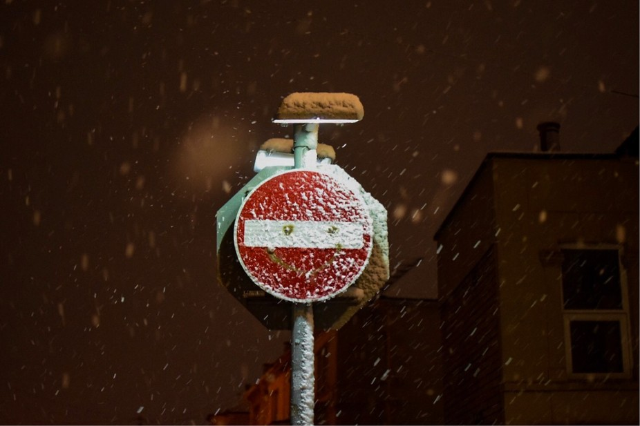 Stop sign covered in snow.