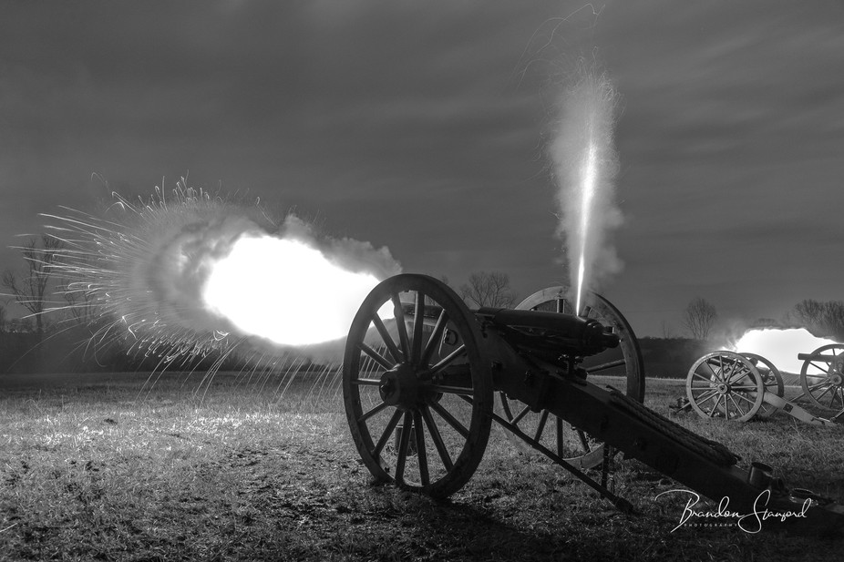 Cannon fire during a night time battle during a Civil War reenactment.