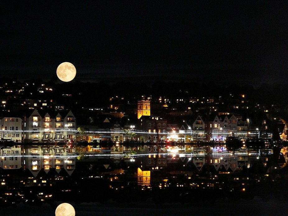 Bright full moon, water reflection, church, town at night