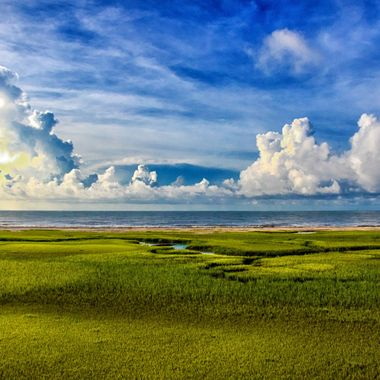 A shot from above of the brilliantly green marsh leading to the deep blue Atlantic