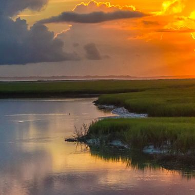 A cloudy summer sunrise as a single dolphin peeks its dorsal fin through the glasslike water