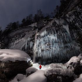 Me under frozen Peričnik waterfall in Slovenia lit up by almost full moon.