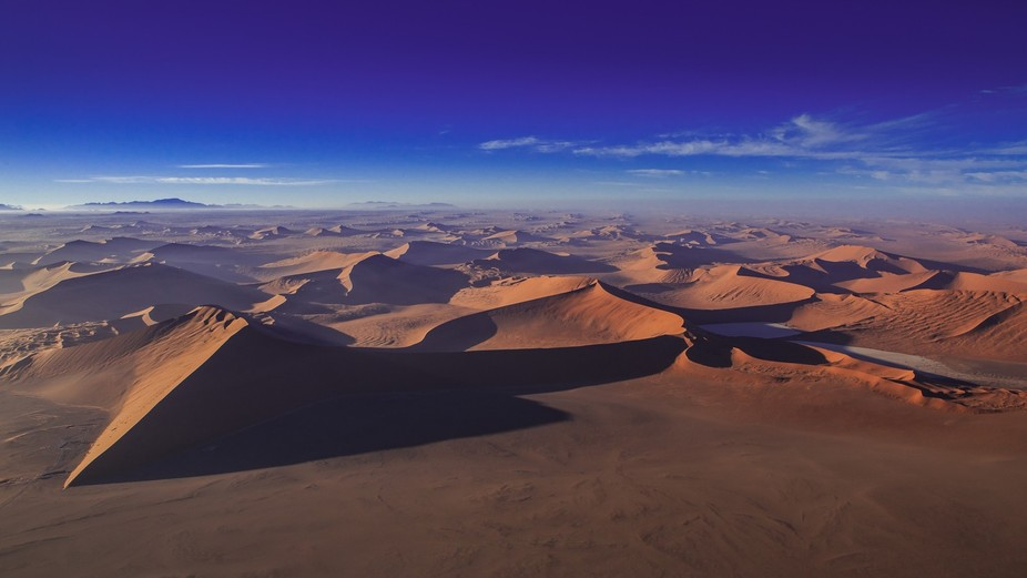 Shortly after sunrise, from a helicopter hovering over the Namib desert you get to see how vast t...
