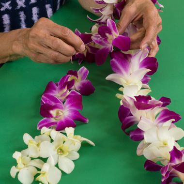 My wife making orchid lei for family.