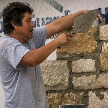 A stone mason at work on a new residence