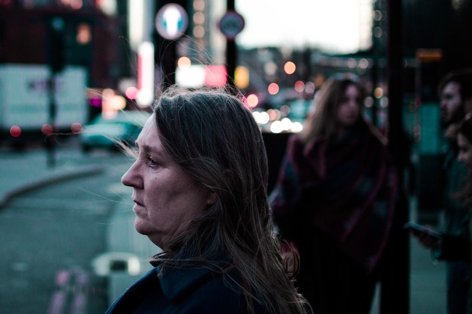Side profile view of a middle aged woman standing in the streets of Shoreditch, London
