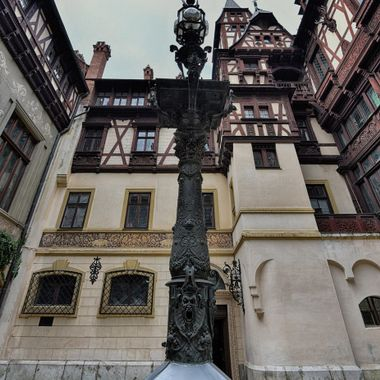 Courtyard at Peles Castle where this fountain is in the center that also is a light post.