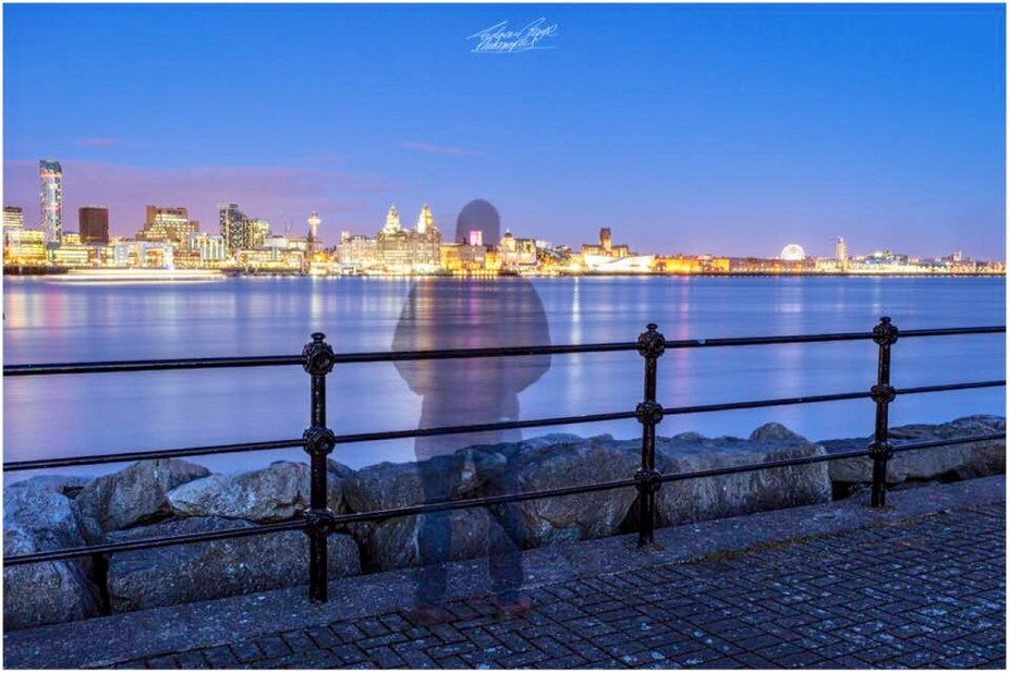 A ghostly person looking across the river mersey at the liverpool skyline