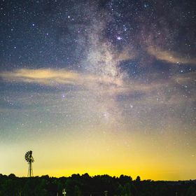 An old windmill is silhouetted by the ambient light at the horizon and the galactic center of the Milky Way Galaxy in the small town of Dawson, P...