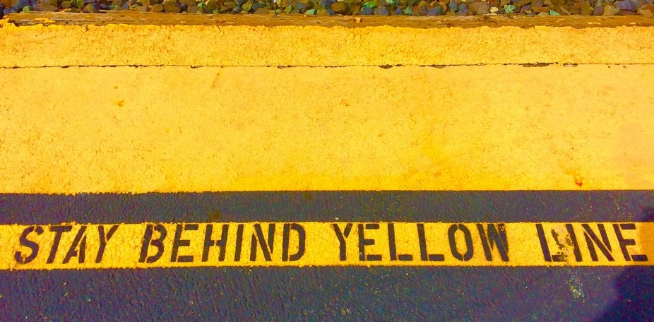 Behind the yellow line markers at nearby train station.