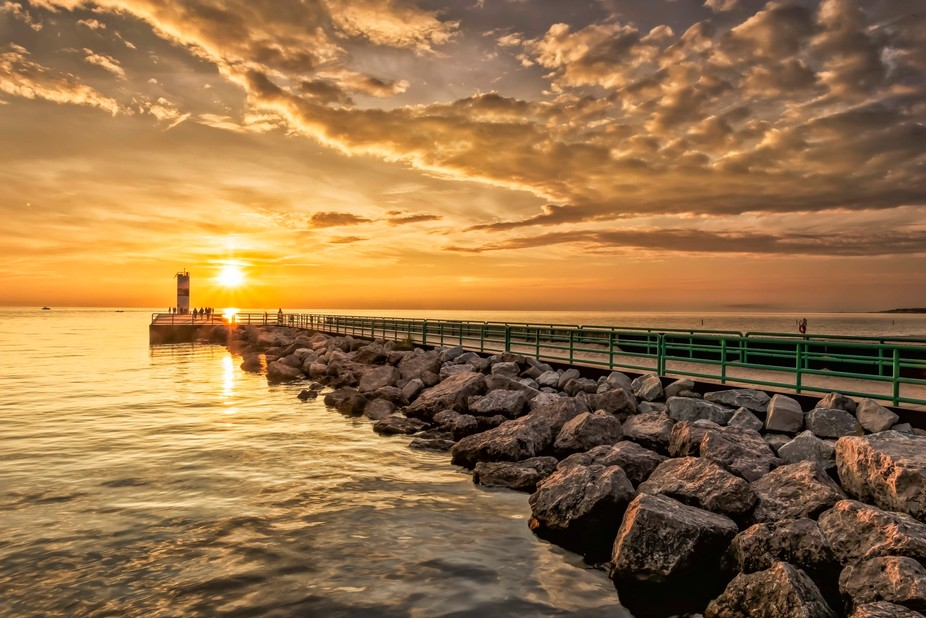 The sky turned gold with the setting sun reflecting off the clouds, the water and the rocks of th...