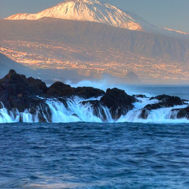 The first sun rays hit the Volcano Teide seen from the north coast of the island.