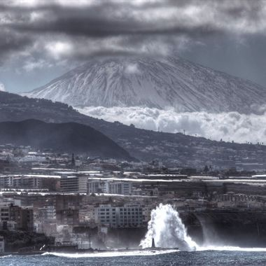 Photo taken from the village of Punta del Hidalgo (TENERIFE) with a 300 mm lense. You can see the huge waves hitting the coast of Bajamar, and at the back the Volcano Teide covered with snow.