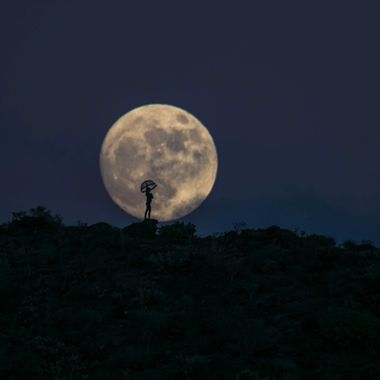 Girl standing on a mountain with an umbrella while the fullmoon raises at the back.,