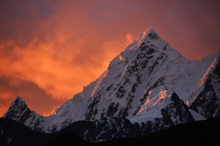 Siula Grande in the Huayhuash of Peru on a fiery sunset. This mountain was made famous by the boo...