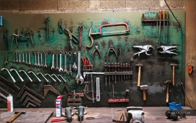 Wall with different metal instruments in little factory room, manufacturing