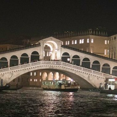 The Rialto Bridge at night shot from the canal.
