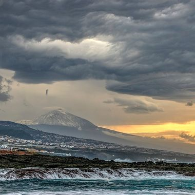 Photo taken in Punta del Hidalgo ( North Tenerife) in winter. Cloudy sky and snow up there in Teide.