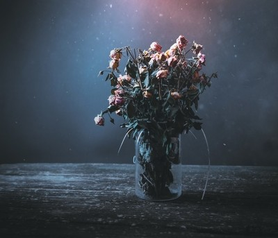 Dried bunch of roses in a vase on a wooden table on a black and
