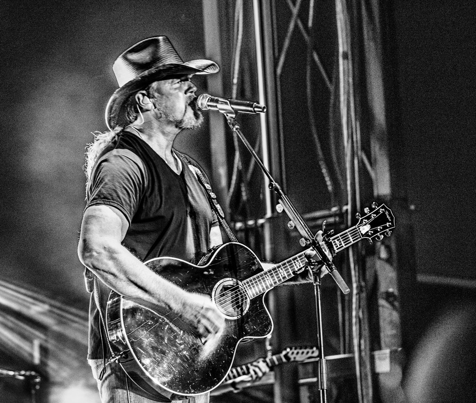 Trace Adkins plays his guitar while singing one of his songs at the Morgan County fair in Jackson...