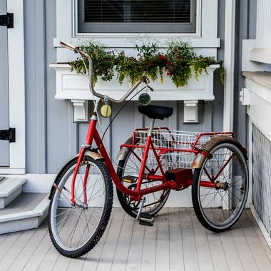 An old red tricycle located on the front porch at The Depot Lodge in Paint Bank, Virginia.