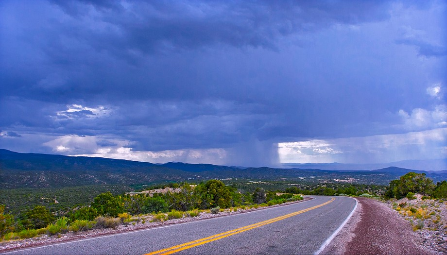 Taken near Cordova, NM at an elevation of about 7,000 ft. New Mexico's wide-open expanses allow one to to view a full rain shaft dropping much needed rain. Although the road seems to heading right to the rain, by the time I reached Nambé the storm had moved on. Details: Canon 40D, Sigma 14MM lens. ISO 400, f/5.6, 1/1250 sec.