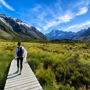My wife heading along the Hooker Valley Track in New Zealand. The snow capped mountain in the background is Mt Cook, the tallest peak in NZ.