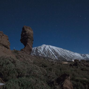 Volcano Teide National Park at night and a photographer taking some shots on the left side.