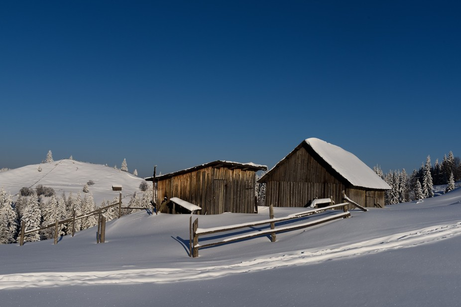A barn and house at the top of the pass between Sucevita and Moldovita in Roumania on a superb morning after over night snow.  Even though it is early a sledge has already passed by