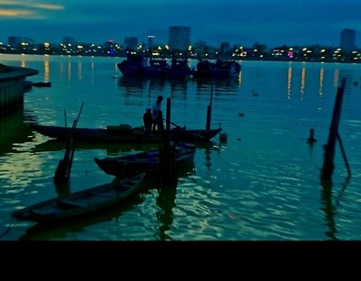Day is done Father & Son parking traditional fishing boat on river running thru modern City of Danang