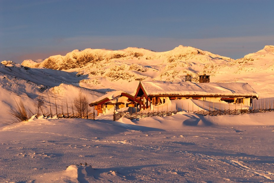 Wonderful light just after sunrise on Christmas day lights this holiday home in Beitostolen. The strong winds have banked the snow almost up to roof height