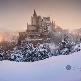Segovia and Alcazar castle on snow covered landscape.