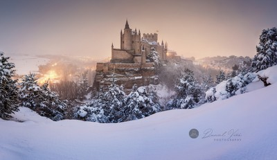 Segovia and Alcazar castle on snow covered landscape.