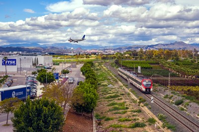 Airplane landing over the shopping center and train
