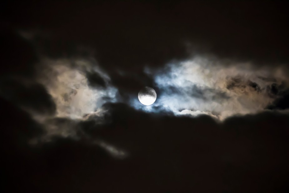 As I was returning home one evening, I saw the moon peek out from between the rain clouds. I park...