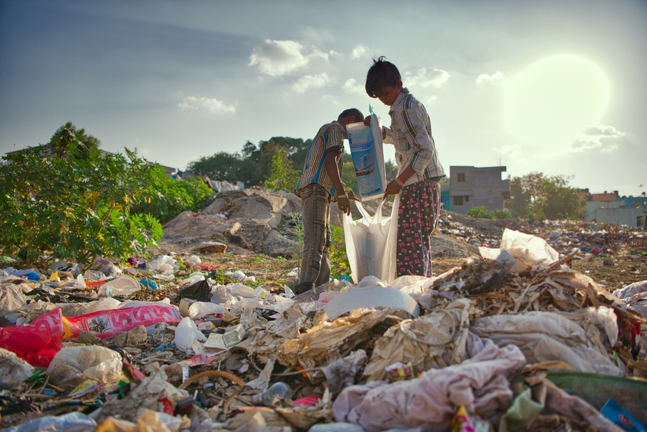 In an area where people just toss their trash and litter an empty lot, 2 boys collect different r...