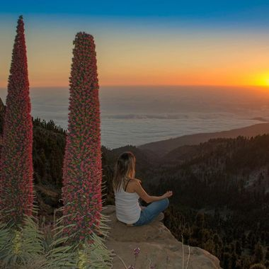 Saray sitting down on top of Tagara Mountains in Teide National park while watching the sunset over the sea of clouds.